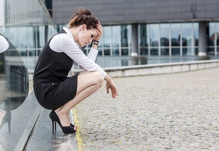 depressed-lady-at-work-crouched-by-window-shutterstock_169783319.jpg