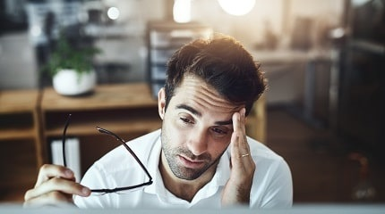 Sick man at work iStock_PeopleImages_SMLL.jpg